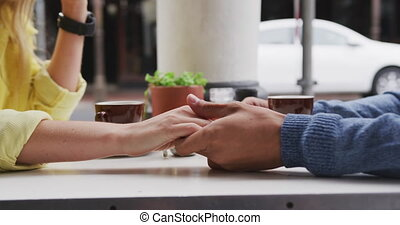 Focus of Caucasian couple holding their hands at terrace coffee
