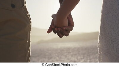 Focus on African American couple holding their hands at beach
