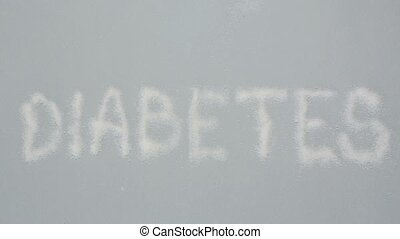Focus on diabetes spelled out in sugar on grey background