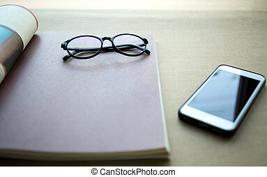 Focus on glasses with cell phone and book