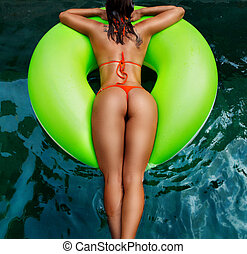 Focus on great looking , perfect shape and tan buttocks with swimsuit. Background is water in swimming pool.