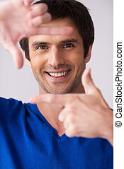 Focus on me! Handsome young man in blue sweater gesturing finger frame and smiling while standing against grey background