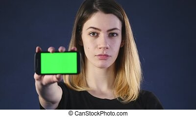 Focus on mobile phone. Young woman hands showing blank smartphone screen isolated on green background and pointing on screen