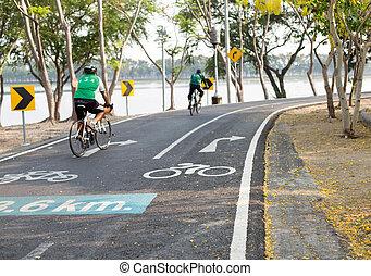 Focus on road sign bicycle lane couple peolple riding bicycle