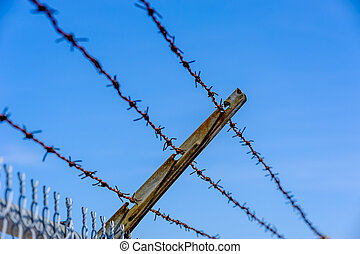 Focus on rusted barbed wires against blue sky.