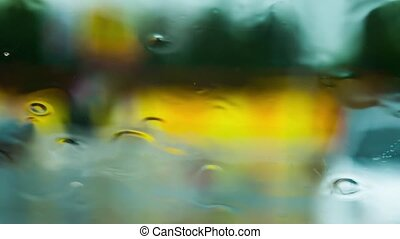 Focus on the glass, the background is blurred, it's raining, the person's figure is passing.