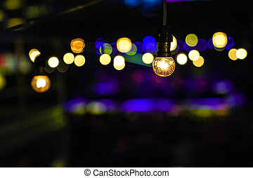 Focus on Vintage circle hanging lamp on the line with blur outdoor concert in the night bokeh background.