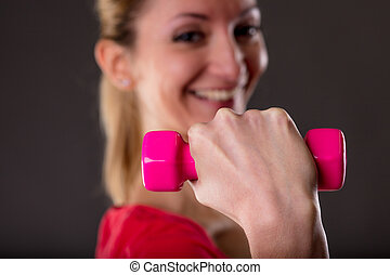 focus on weight lifting by a smiling woman