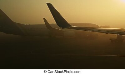 focus out from closeup view on two large aircraft silhouettes against bright sun