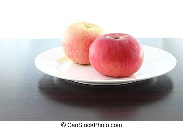 Focus red near apple dish on wooden table.