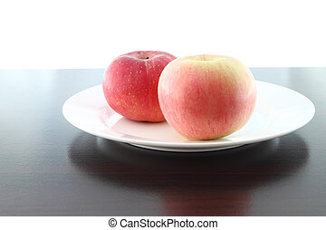 Focus soft near apple dish on wooden table.
