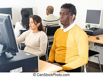 Focused African American sitting in pc room in public library