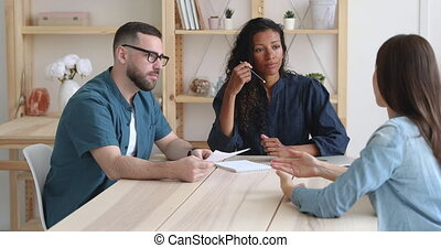 Focused african and caucasian employers recruiters interviewing female job applicant listening to vacancy seeker speaking about qualification work experience at office meeting, hr and recruit concept