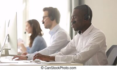 Focused african call center agent wear wireless headset consulting customer