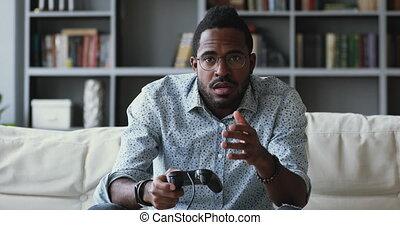 Focused african ethnicity guy using joystick, winning losing...