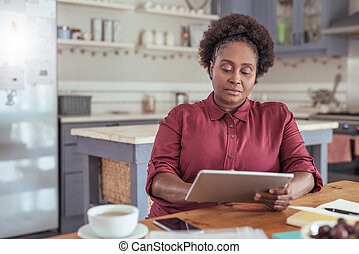 Focused African woman working on a digital tablet at home -...