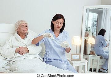 Focused appealing nurse preparing medication