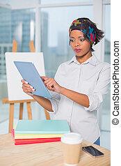 Focused artist using tablet in her studio