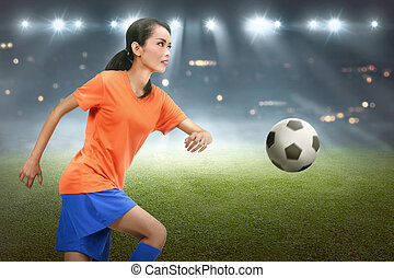 Focused asian soccer player woman showing her skills