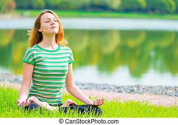 focused athlete relaxes in a lotus position on the nature