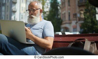 Focused bearded gentleman working outdoors - Busy routine....