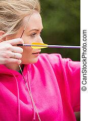 Focused blonde practicing archery wearing pink jumper