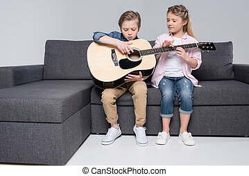 focused brother and sister playing on guitar together while sitting on sofa