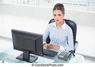 Focused brunette businesswoman sitting at her desk