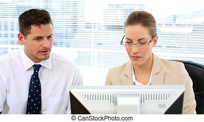 Focused business team looking at computer