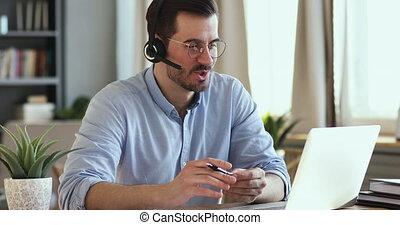 Focused businessman in eyeglasses holding video conference ...