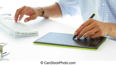 Focused businessman working on hi computer and tablet in his...