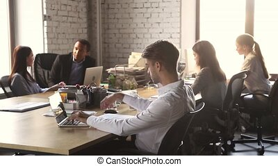 Focused businessman working with laptop sitting at table in office
