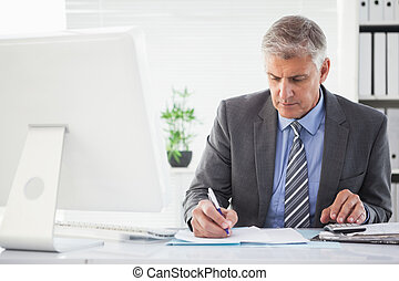 Focused businessman writing something down in his office