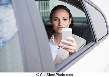 Focused businesswoman using her phone