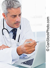 Focused doctor watching something on his laptop
