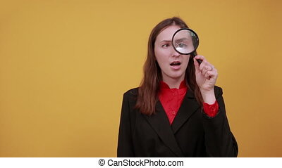 Focused Female Holds A Magnifying Glass To Eye, Looks ...