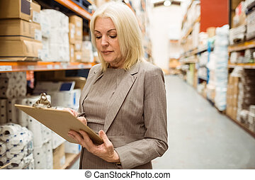 Focused female manager holding clipboard in a large...
