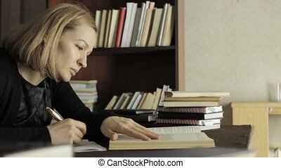 Focused female student working with books in a library in university college. tired student preparing for exams