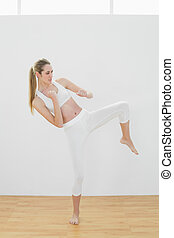 Focused fit woman wearing sportswear doing martial arts