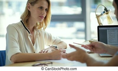 Focused girl listening to groupmate explaining her...