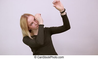 Young Blonde Woman In Black Sweater With Stylish Watch On White Background, Focused Girl Looking Through Her Hands Imitates A Telescope. Researcher, Scientist. Concept Of Smart And Purposeful People