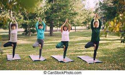 Focused girls yogini are standing in Vrksasana pose Tree...