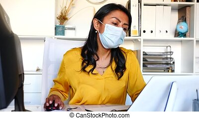 Portrait of confident Latina wearing medical mask working on computer in office. New life reality during coronavirus pandemic
