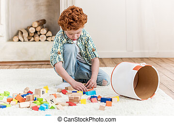 Focused little boy playing with cubes on floor at home