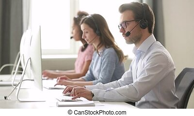 Focused male call center agent in wireless headset helping customer