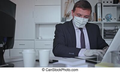Focused male in disposable personal protective equipment working in business office using laptop, new normal due to coronavirus outbreak