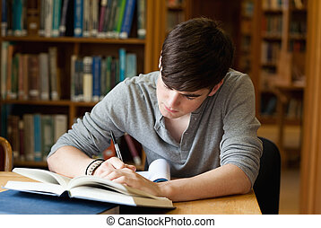 Focused male student working in a library