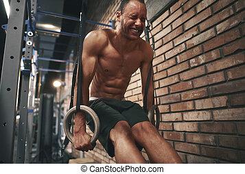 Focused man using gymnastics rings