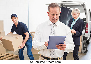 Focused manager holding tablet in front of his colleagues