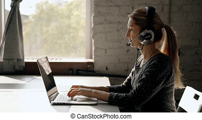 Focused mature woman working in call center using headset -...